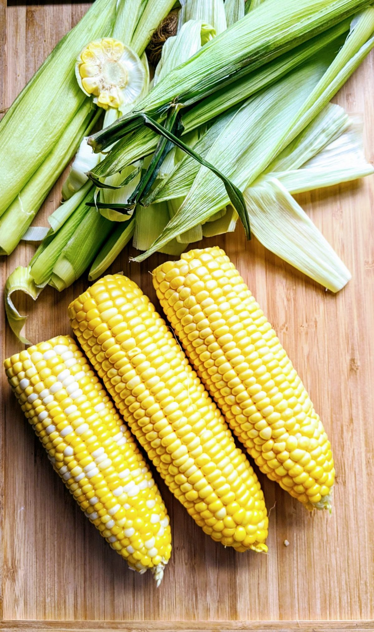 Three pieces of corn on the cob with husks shucked off