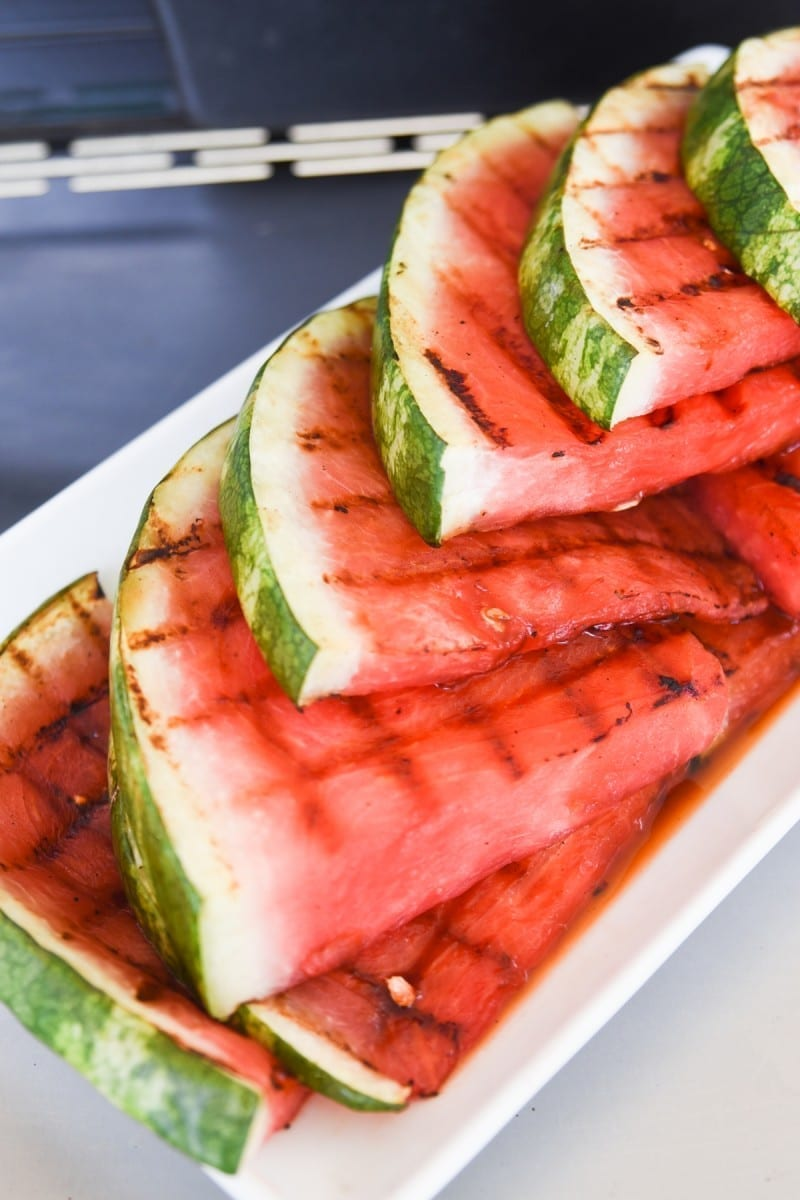 Several pieces of grilled watermelon sitting on a white platter