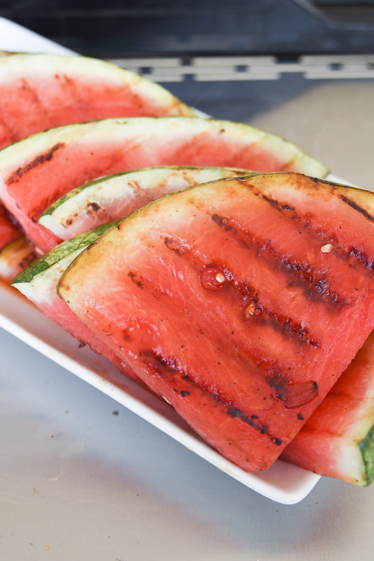 Front view of grilled watermelon on a platter