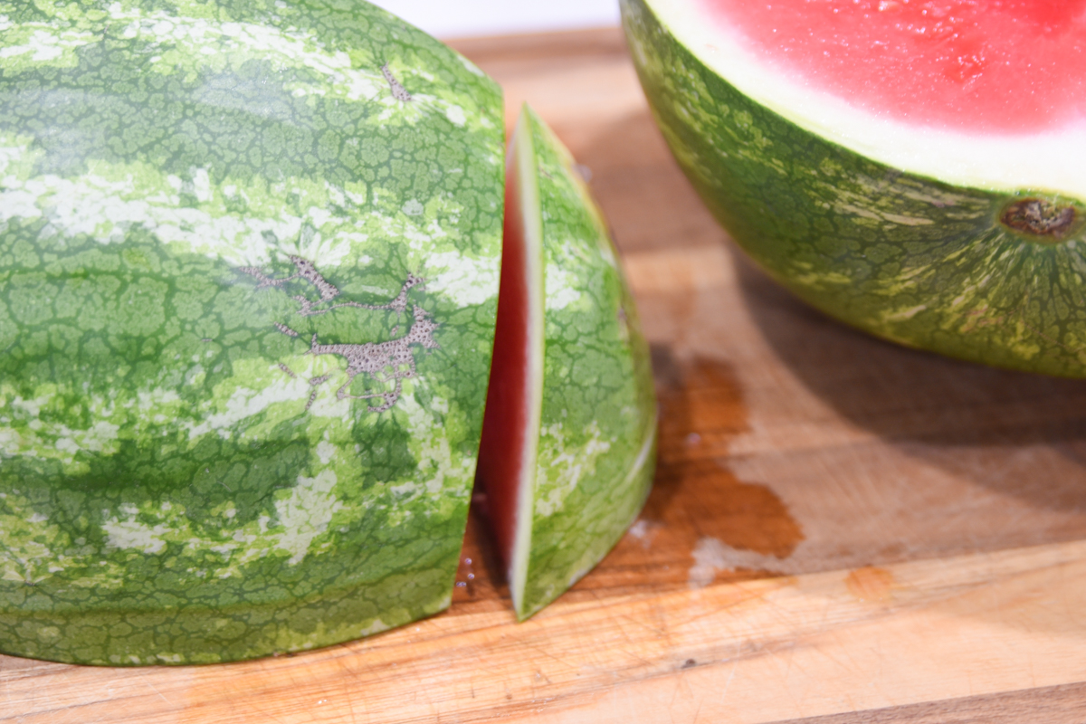 slice of a watermelon by a larger melon