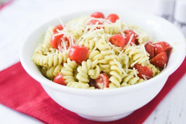 pesto pasta salad with grape tomatoes,parmesan and pesto in a white bowl