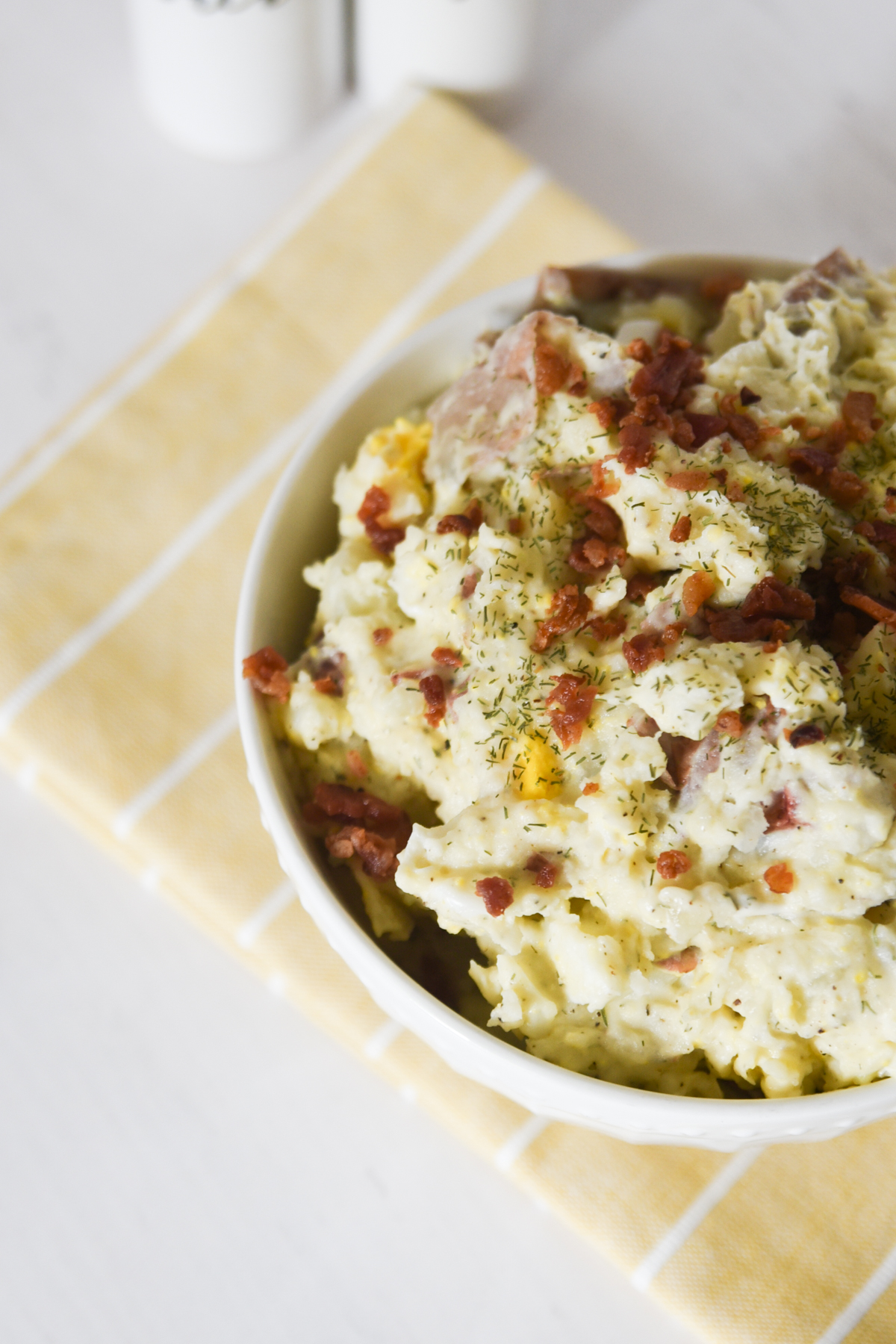 Top view of red potato salad with bacon bits.