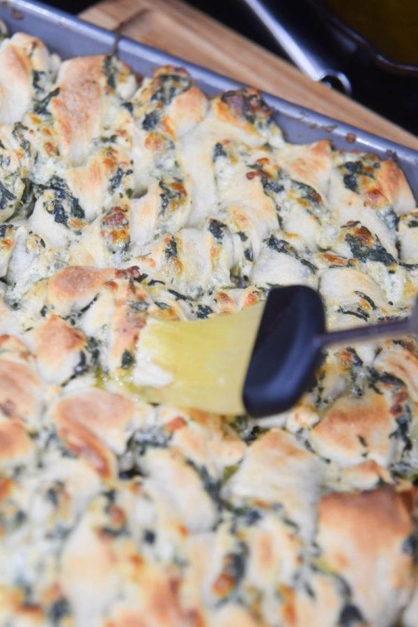 brushing butter on top of breadsticks